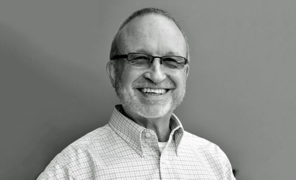 A professional headshot of david machles wearing a button down shirt and glasses smiling into the camera.