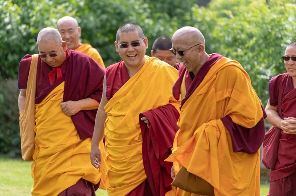 His Eminence Ling Rinpoche walking outside and laughing with four other monks.