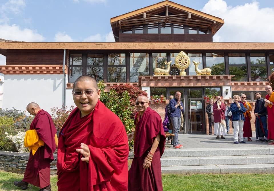 His Eminence Ling Rinpoche smiling at the camera as Rinpoche walks away from the nalanda monastery building while students smile and hold khatas.