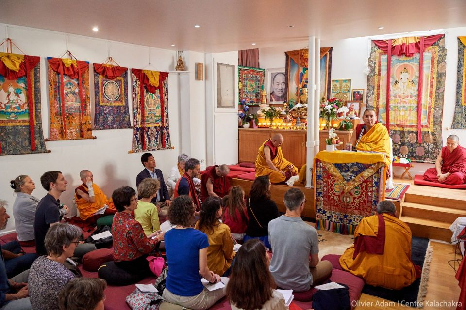 His Eminence Ling Rinpoche seated on a throne in the front of the colorful gompa teaching to an audience of students seated on meditation cushions.