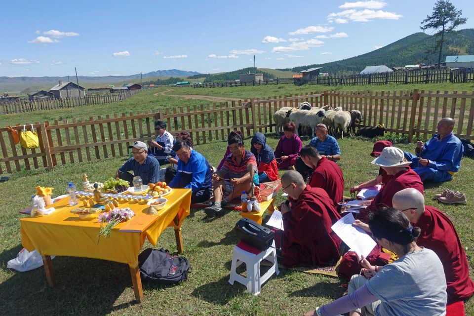 A group of people seated on the grass inside of the fenced in field for the liberated animals doing practices in front of a table holding holy objects and offerings.