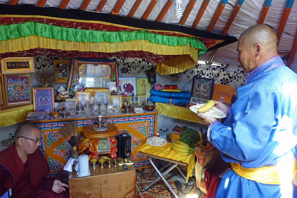 The interior of a traditional mongolian tent with many holy objects hung on the wall and placed on an altar with one monk seated and another person standing wearing bright blue holding an offering of a banana and other food items on a small white plate.