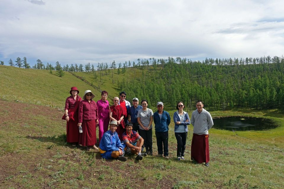 A group of ten people some of them ordained sangha posing for a photo on an extinct volcano with green trees in the background.