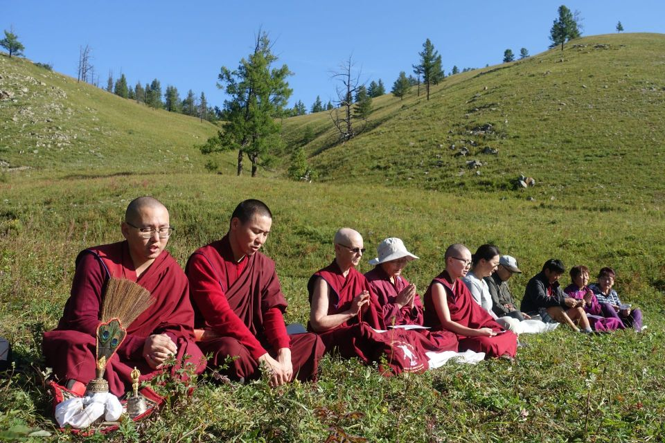 Five ordained sangha and five lay people seated in the grass in a row reciting prayers in the sunshine.