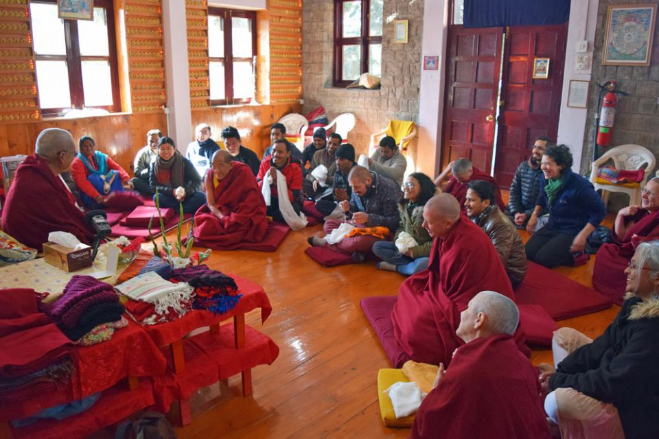 Lama Zopa Rinpoche and tushita meditation center staff seated facing each other smiling and talking inside of a room with sunlight streaming in through the windows.