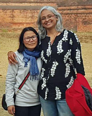 pema wangmo and archhana kombrabail standing together posing for the camera in front of a building at nalanda in bihar india.