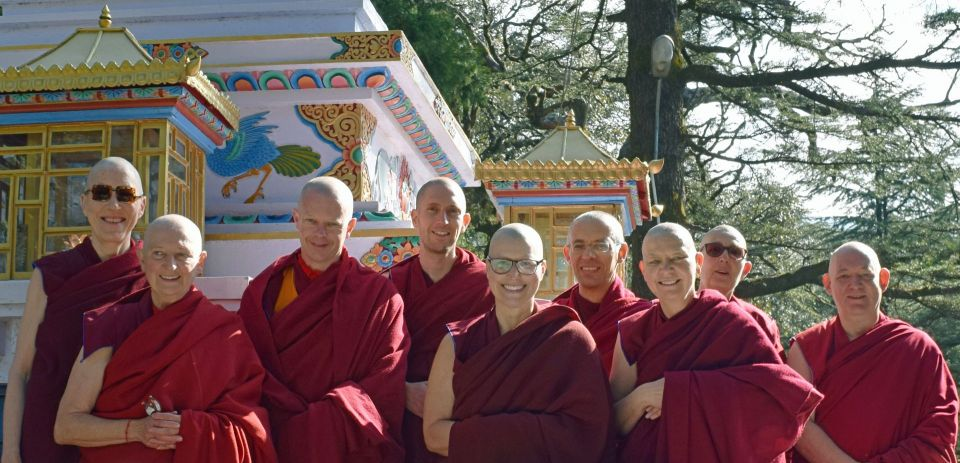 Geshe Tenzin Namdak posing for a photo with eight new western monks and nuns in front of Lama Yeshe's stupa at tushita meditation centre.