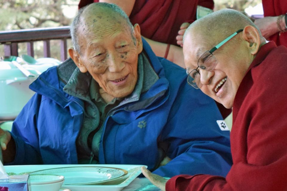 Khylonga Rato Rinpoche and Lama Zopa Rinpoche seated outdoors at a table laughing together after finishing a meal.