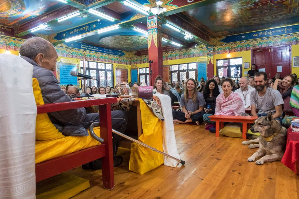 Khylonga Rato Rinpoche teaching to a full room of young students who are all smiling and looking at dog nyingje chenmo seated on the floor looking at Khylonga Rato Rinpoche.