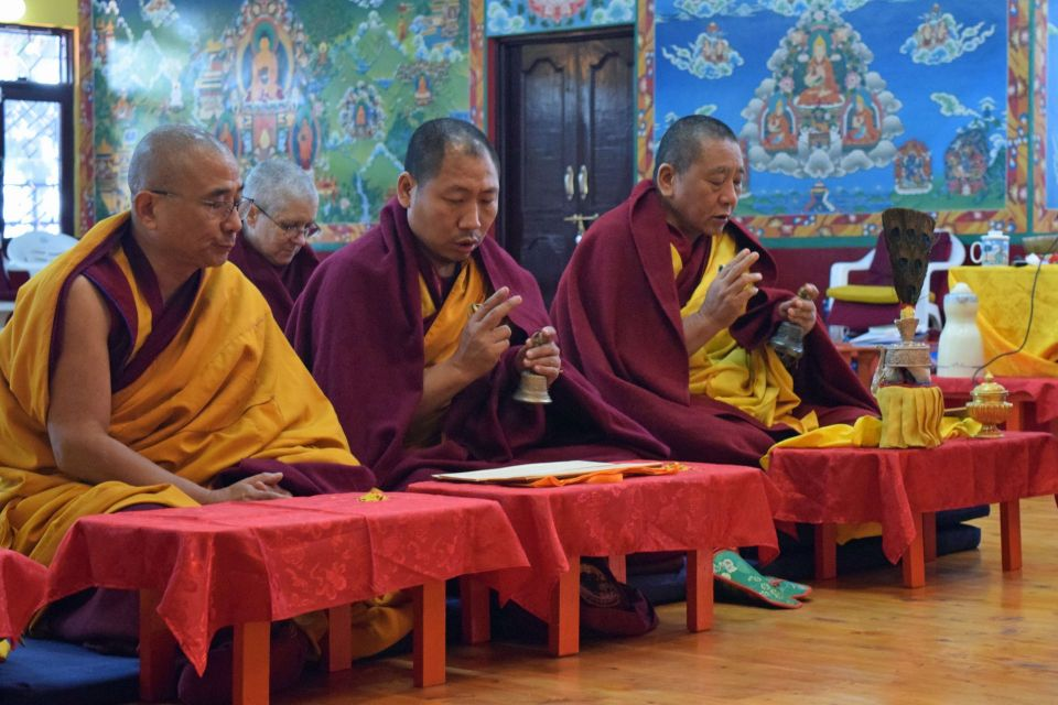 Venerable Tenzin Drolma and three monks seated performing a puja inside of the beautifully appointed tushita meditation centre gompa.