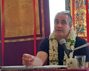 Sixte vincotte wearing a flower lei seated in front of a microphone with thankgas behind him as he speaks.