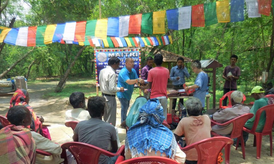 Kiran Lama standing next to a table and facing an audience of villagers seated on red plastic chairs underneath colorful prayer flags and offering donated items to people one person at a time.