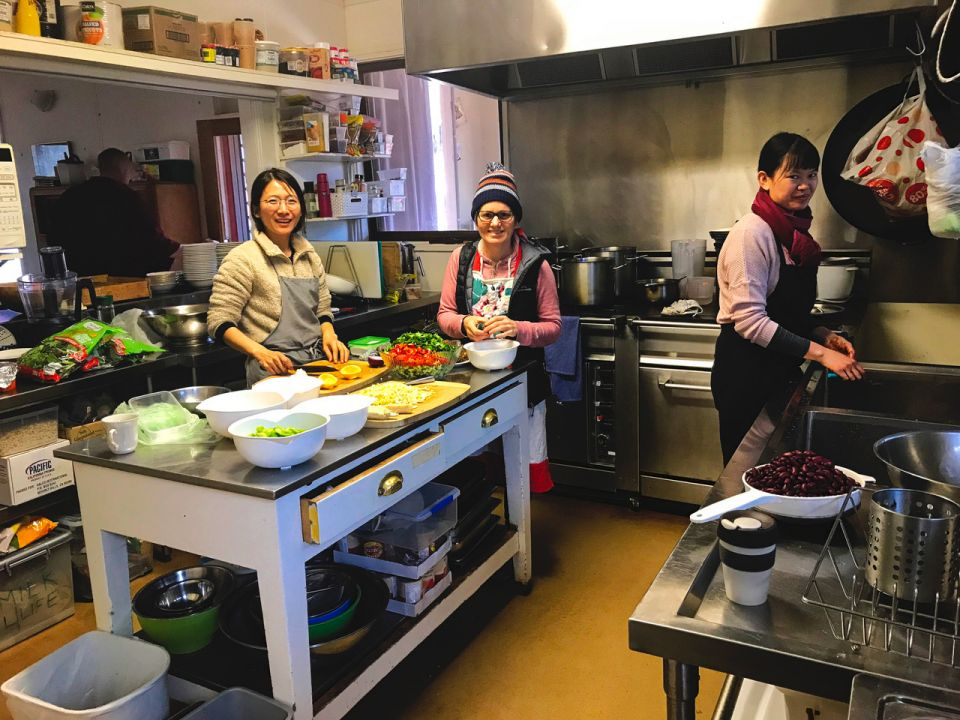 Three people wearing aprons and standing in an industrial kitchen pausing in their work preparing food to smile for the camera.