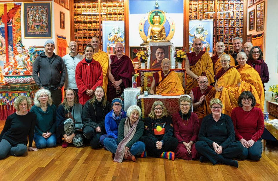 A group of ordained and lay students standing around Geshe Thubten Rabten and smiling into the camera for a group photo.