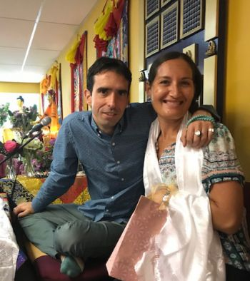 Nicole zito wearing a white khata around her neck posing for a photo with Tenzin Osel Hita who has his arm laid across her shoulders.