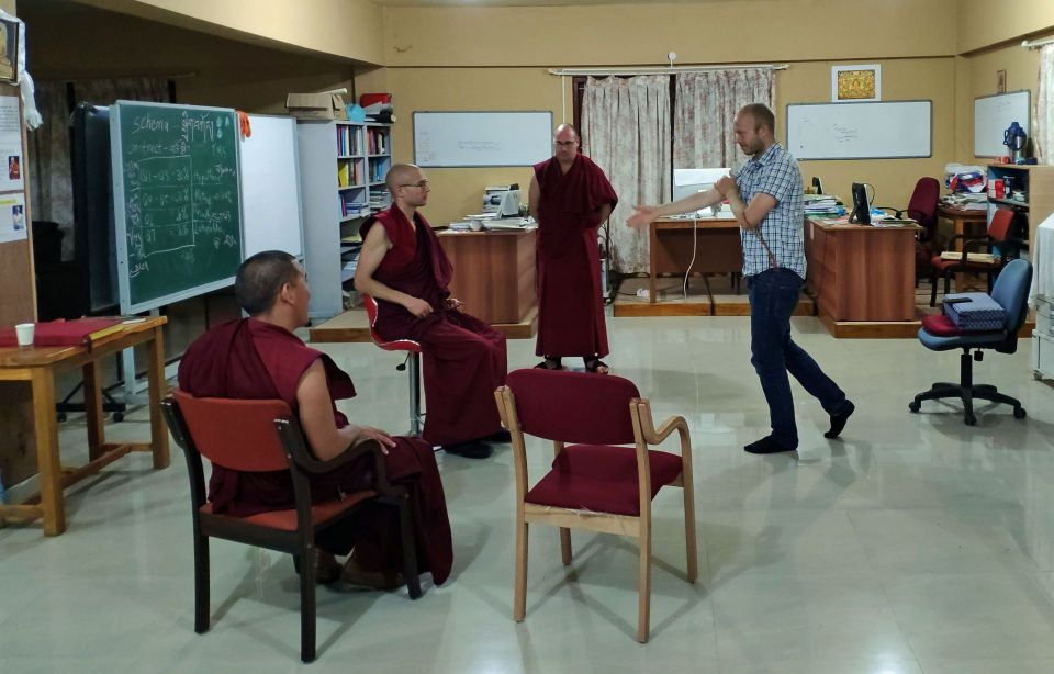 Venerable Tenzin Gache seated in a chair and facing scientist amir moye as the two engage in debate.