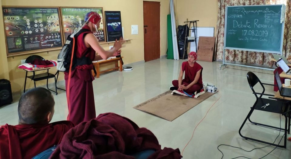 Two monks debating while wearing tools needed to conduct the scientific experiment.