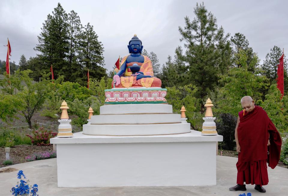 Lama Zopa Rinpoche circumambulating Medicine Buddha statue