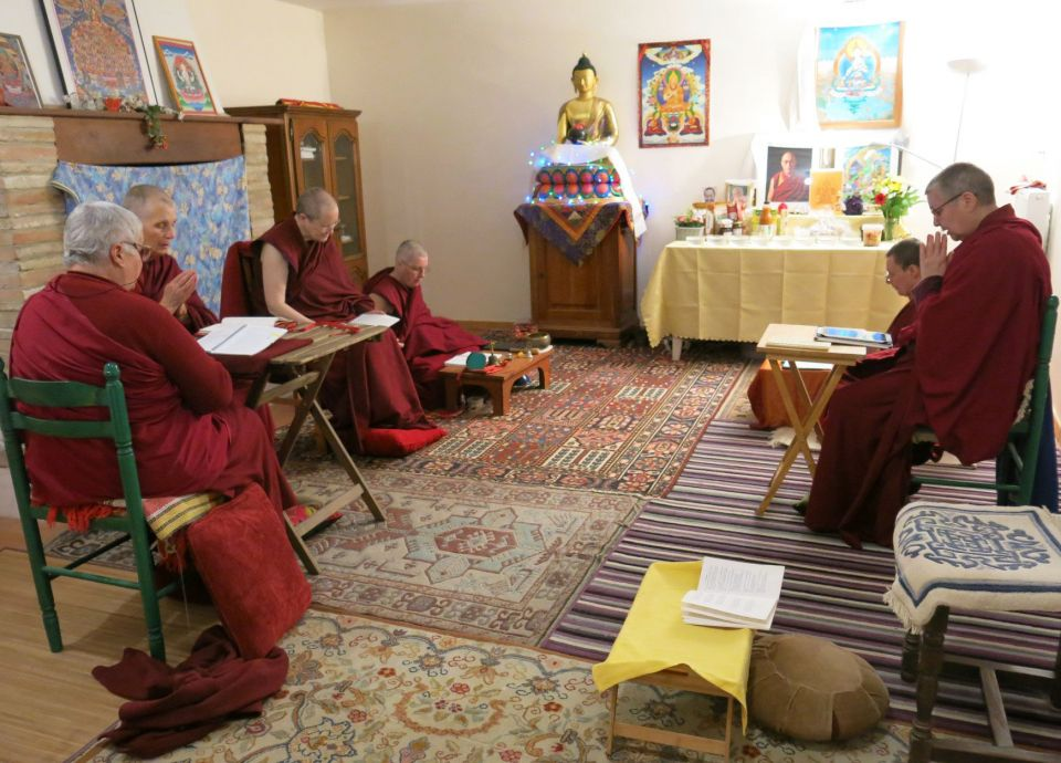 Five western nuns seated in front of an altar engaged in practice together.