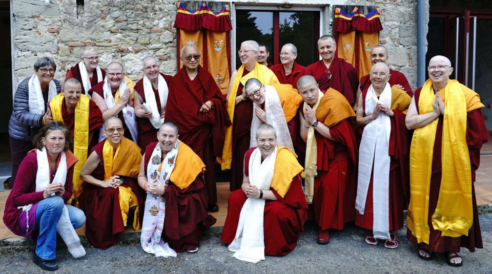 Group of non-himalayan nuns smiling and laughing posing for a photo with Lama Zopa Rinpoche outside in the sunshine in front of a Dorje Pamo Monastery stone building.