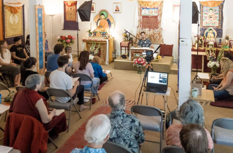 Tenzin Ösel Hita seated at the front of the room smiling and speaking to an audience of lay people and nuns inside of the ocean of compassion center gompa with thankgas on the walls.
