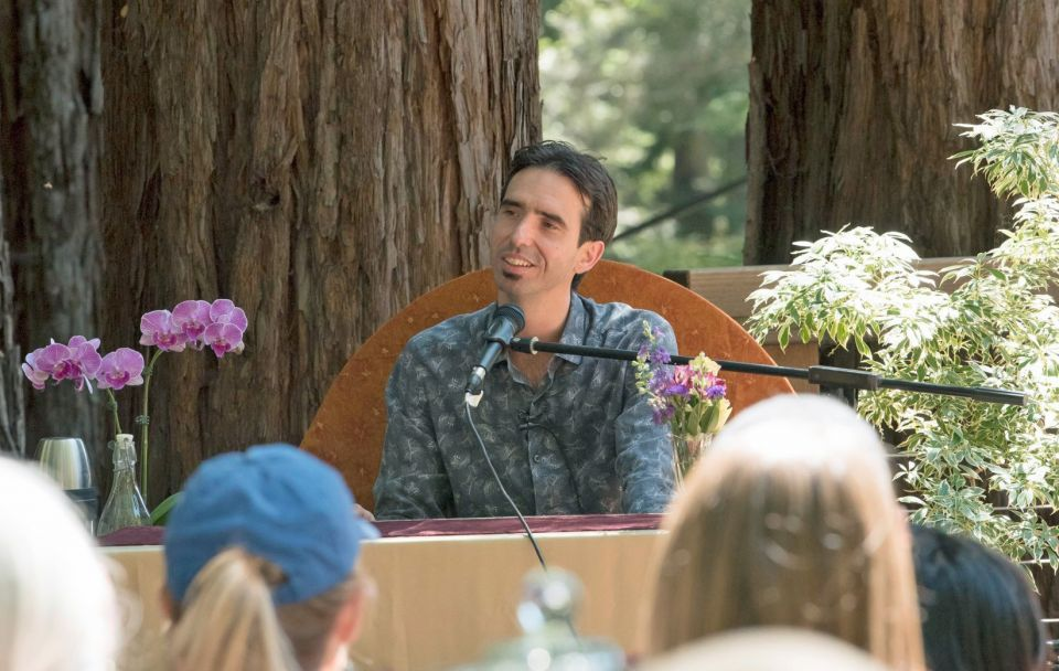 Tenzin Ösel Hita seated outdoors in front of beautiful old trees in the woods smiling at an audience listening to him talk.