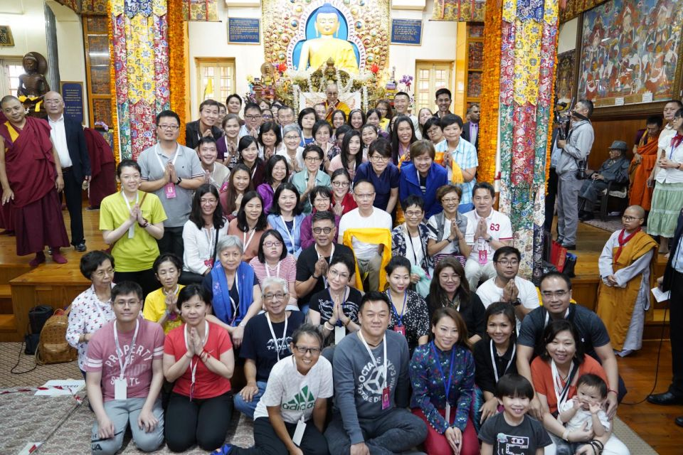 A large group of adults and a few small children posed for a photo with the smiling His Holiness the Dalai Lama seated on his throne in front of a golden Buddha statue in the main temple.