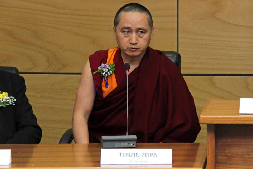 Geshe Tenzin Zopa in the process of speaking while seated behind the table with a microphone on top and a sign in front of him on the table that says Tenzin Zopa Buddhism.