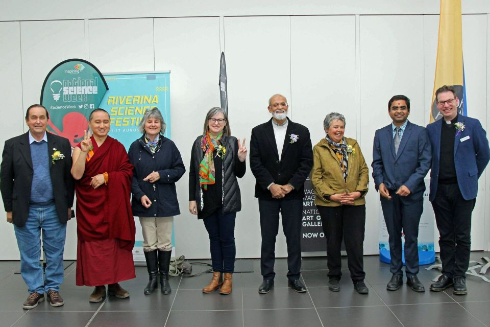 The seven people who sat on the panel are standing together and smiling in a white walled conference room and Geshe Tenzin Zopa and Toni Coleman are smiling and making the peace sign with one hand each.