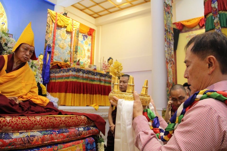 Tan Hup Cheng holding the mandala and white khata with arms extended towards Lama Zopa Rinpoche seated on the throne in the Amitabha Buddhist Centre gompa.