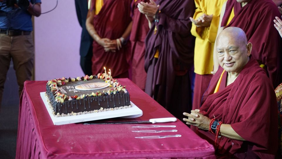Lama Zopa Rinpoche seated behind a table covered in a maroon table cloth with a large chocolate cake.