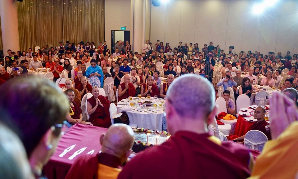 Lama Zopa Rinpoche seated at a table on a stage facing the audience seated at round banquet styled tables covered in white table cloths looking up towards Rinpoche and the camera smiling.