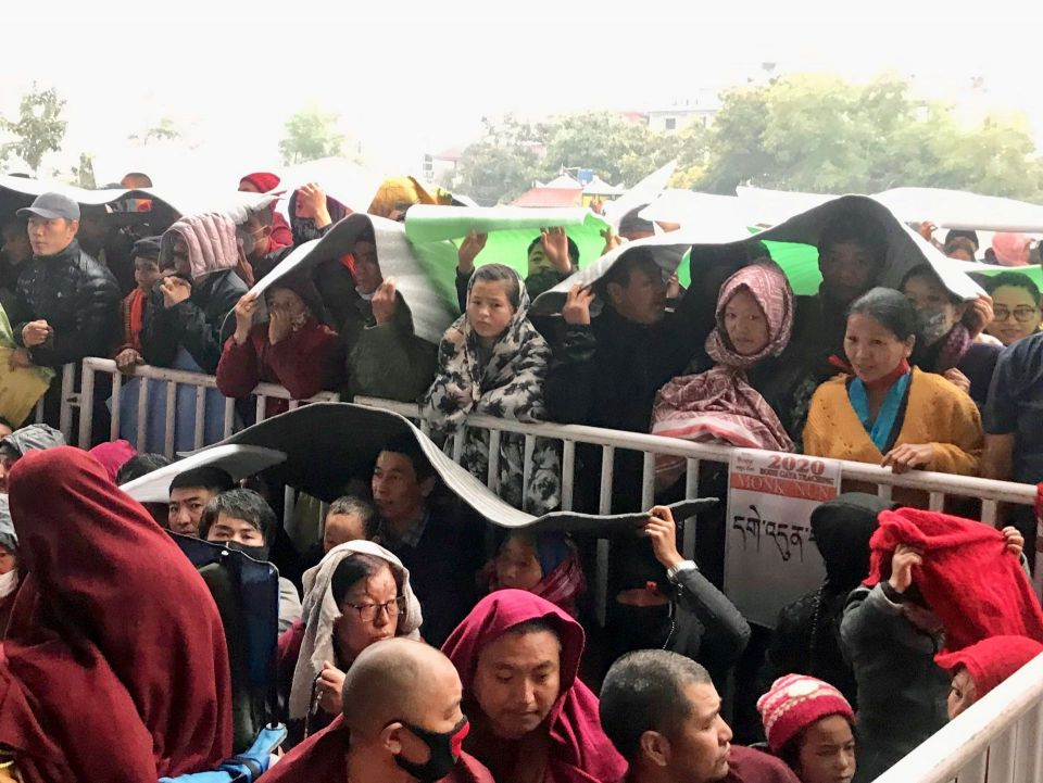 Lay and monastic devotees standing along a fence holding rectangular foam mats over their heads to keep dry in the falling rain.