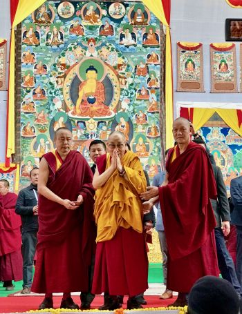 His Holiness standing on the stage in front of a huge thangka of Shakyamuni Buddha with his hands folded together in prayer at his chest looking out into the crowd.
