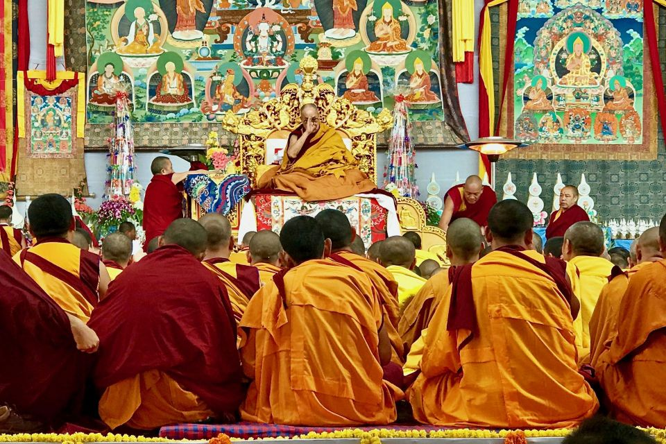 His Holiness the Dalai Lama seated on a throne in front of huge colorful thankgas facing rows of seated monastics on the stage.
