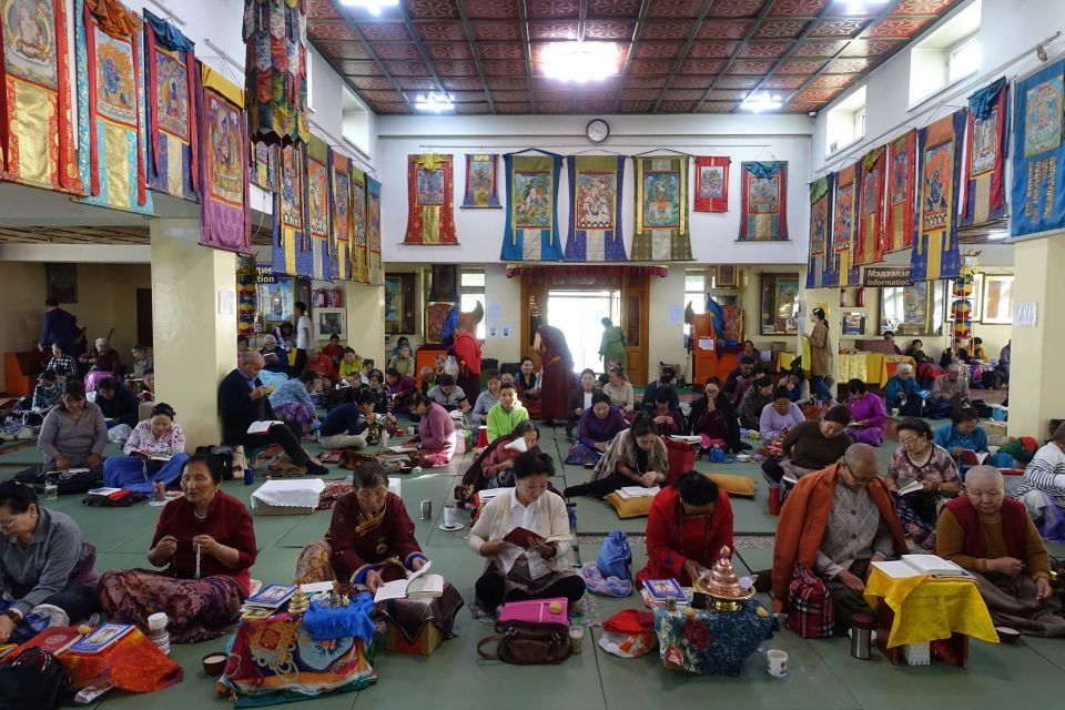 Colorful gompa with large number of people seated on the ground doing group practice while facing the camera.