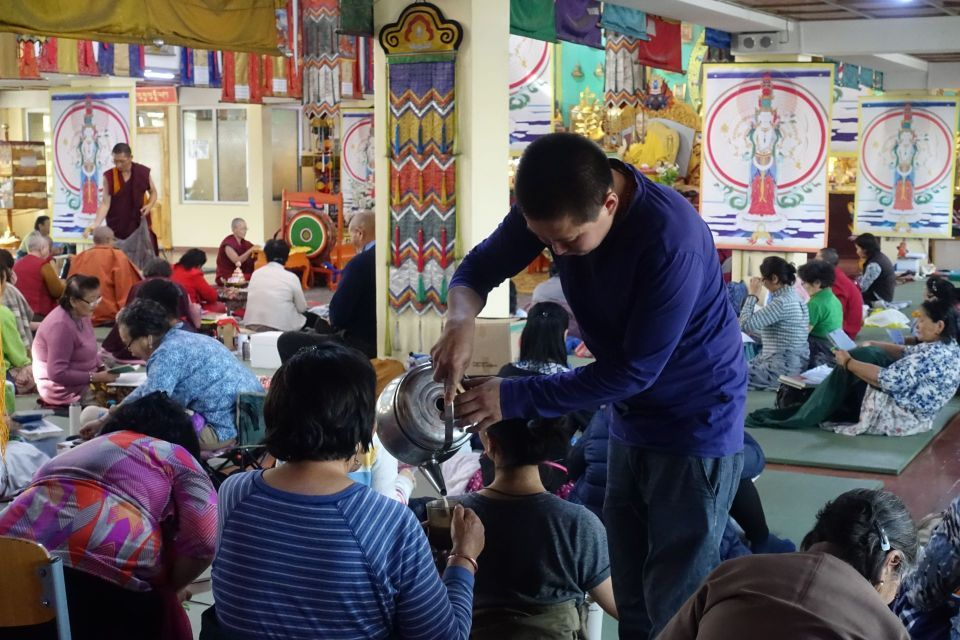A young lay volunteer bent over serving tea to a retreatant from a silver colored tea kettle in the colorful gompa.