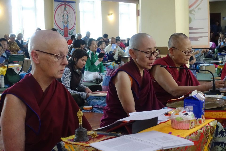Three nuns seated in front of low tables engaged in practice in a colorful gompa.