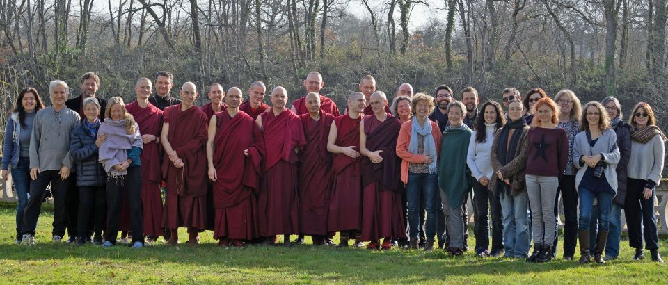 32 people including 11 monastics standing together outside posing for a group photo.