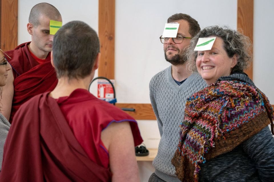 Five people standing in a circle with post-it notes stuck to their foreheads with text written on each one engaged in a group discussion.