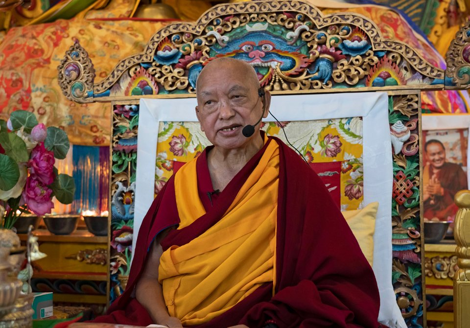 Lama Zopa Rinpoche sitting on teaching throne in Kopan's gompa giving a teaching