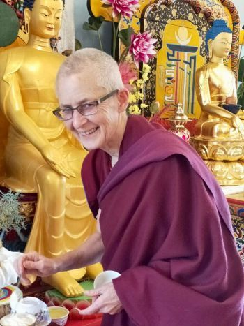 Venerable Tenzin Tsapel smiling in front of two golden Buddha statues.