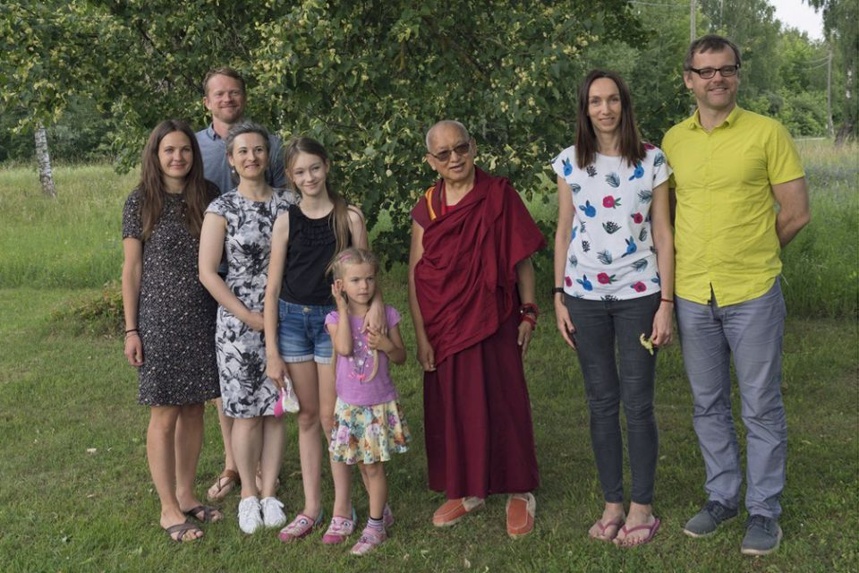 Lama Zopa Rinpoche standing outside on green grass underneath a large tree with several adults and children posing together for a photo.