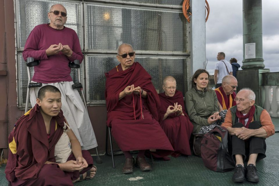 A small group of people gathered around Lama Zopa Rinpoche making prayers together in the open air overlooking the city of Riga.