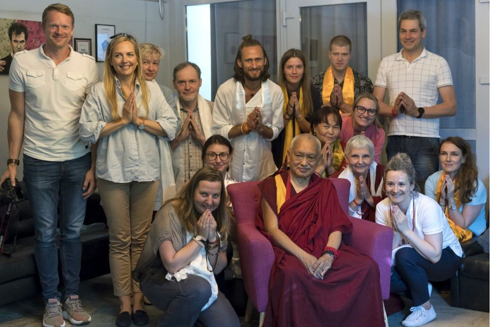 Fifteen students some wearing khatas and many with hands folded gathered around Lama Zopa Rinpoche for a photo.
