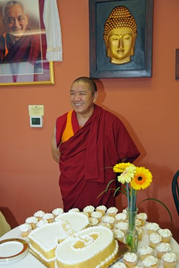Geshe Gelek standing in front of a large cake in the shape of the number twenty.