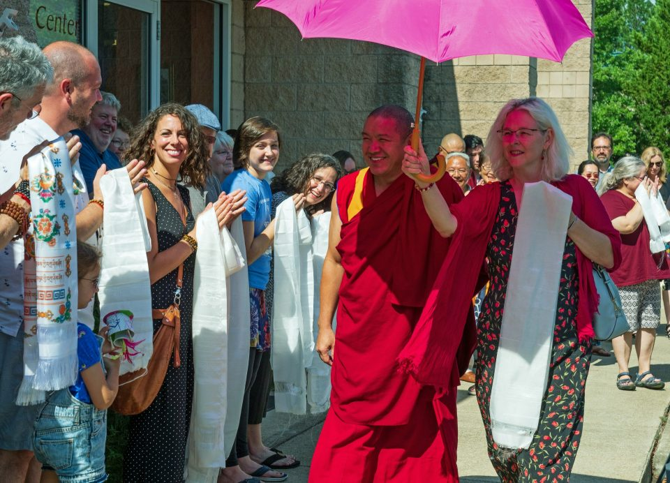 Geshe Gelek walking down the sidewalk passing by a row of students with khatas greeting him and Geshe Gelek protected under a hot pink umbrella held by another student.