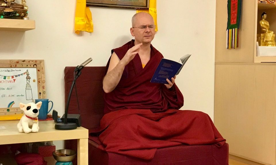 Venerable Fedor Stracke seated on a maroon fabric covered chair with the text used for the retreat in his left hand and gesturing with his right hand. He is seated between a statue of the Buddha on a countertop and a low table with a stuffed toy dog on top.