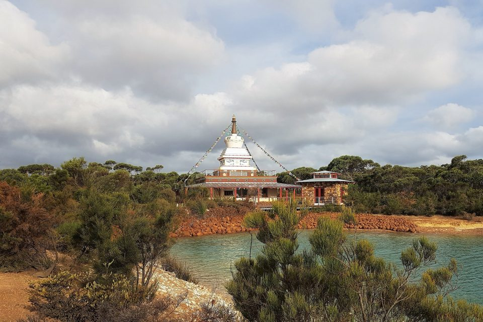 A beautiful stupa atop of a low one story building just next to a small stone building in a bushland setting next to a small lake with a blue sky and clouds overhead.