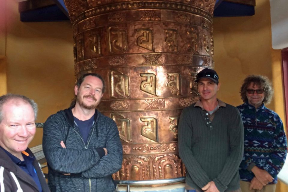 Four people standing in front of a large golden colored prayer wheel posing and smiling for the camera.